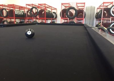 Custom black 8 Ball Motorcycle pool table being installed in 8 Ball Motorcycle Tires Store #1